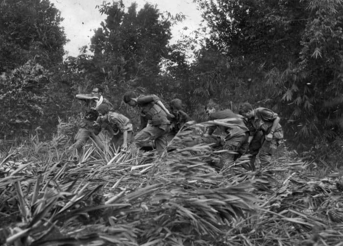 Life magazine photographer Larry Burrows (far left) struggles through elephant grass and the rotor wash of an American evacuation helicopter as he helps GIs carry a wounded soldier on a stretcher from the jungle to the chopper in Mimot, Cambodia on 4 May 1970. The evacuation came during the US incursion into Cambodia. Burrows was killed on 10 February 1971, along with the photographer who took this picture, Henri Huet, and two other photojournalists – Kent Potter of UPI and Keisaburo Shimamoto of Newsweek – when their helicopter was shot down over Laos Photograph: Henri Huet/AP