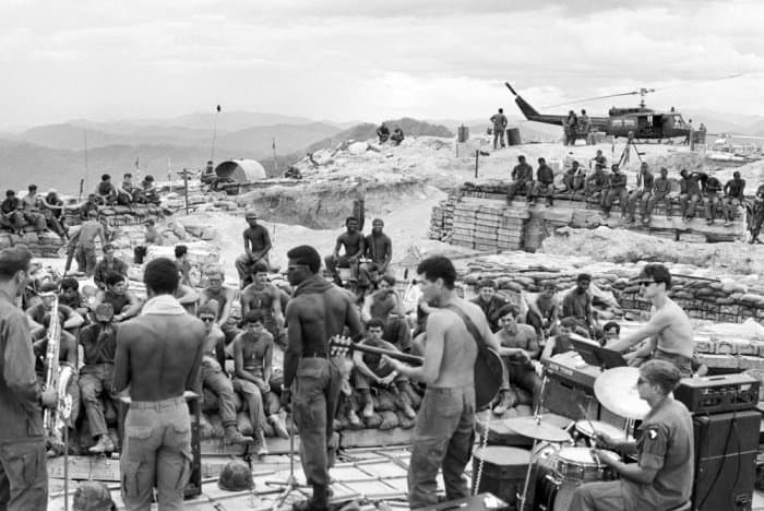 GIs of the 3rd Brigade, 101st Airborne Division, launch into a rock session while surrounded by symbols of the war: wooden bunkers, helicopter and sandbags, in July 1970. The soldiers were dug in at Firebase Kathryn on a hill south of the DMZ Photograph: Giancarlo Meyer/AP