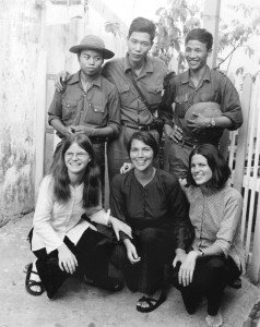"""Claudia Krich, kneeling at left, is one of three American women and 12 Americans altogether who stayed in Vietnam after the fall of Saigon on April 30, 1975. Here, they pose with three North Vietnamese soldiers who were eager to have their photo taken with American women. """"They couldn't imagine they were meeting American women,"""" Krich remembers. """"They had cameras and took lots of pictures. This picture was taken in our little alley where we lived."""" Claudia Krich/Courtesy photo"""