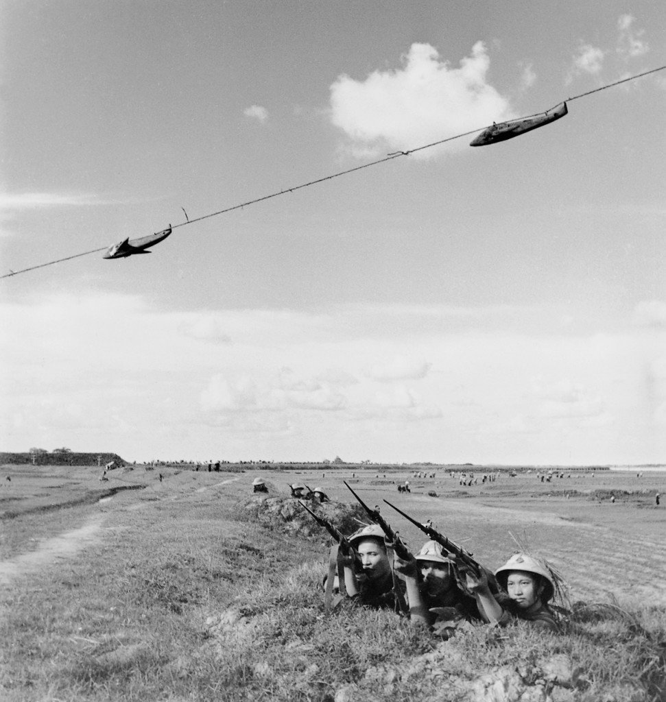 """September 1965 Using overhead targets, a militia company practices firing ahead of speeding aircraft in Thanh Tri. Even using antiquated WWII rifles such as these, the Vietnamese were able to cripple or down many U.S. aircraft. This militia group, Company #6 of the Yen My Commune, earned the title of """"Excellent Militia"""" three years in a row. IMAGE: MINH DAO/ANOTHER VIETNAM/NATIONAL GEOGRAPHIC BOOKS"""