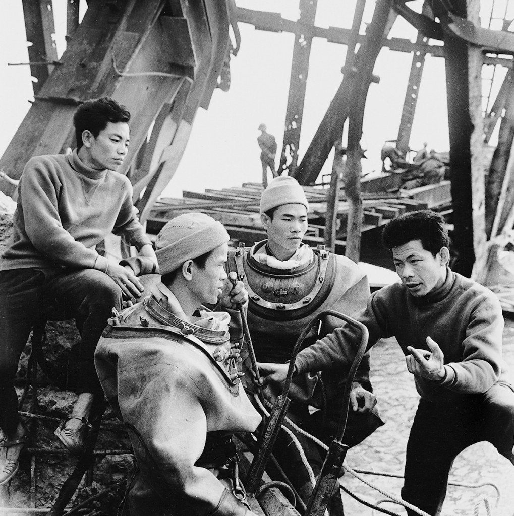 1973 Construction workers discuss repairs of the bombed out Ham Rong Bridge, in central North Vietnam. The only route across the Ma River for heavy trucks and machinery, the bridge was heavily defended, and several U.S. planes were shot down nearby. An American MIA search team found pilot remains there. IMAGE: UNKNOWN PHOTOGRAPHER/ANOTHER VIETNAM/NATIONAL GEOGRAPHIC BOOKS