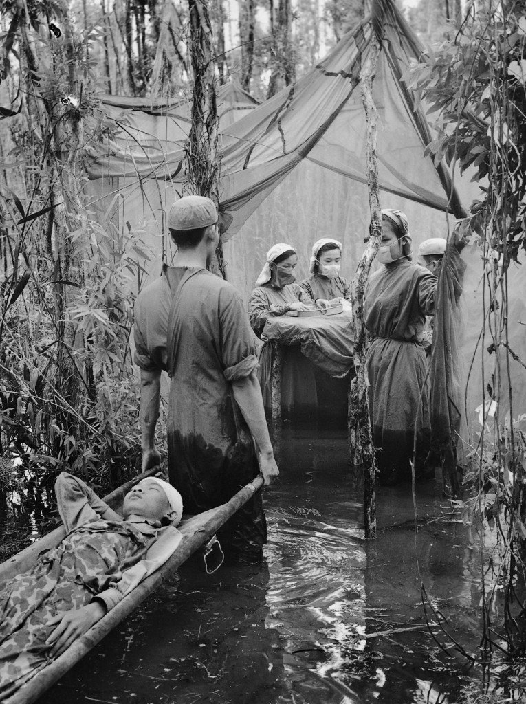 Sept. 15, 1970 A victim of American bombing, ethnic Cambodian guerrilla Danh Son Huol is carried to an improvised operating room in a mangrove swamp on the Ca Mau Peninsula. This scene was an actual medical situation, not a publicity setup. The photographer, however, considered the image unexceptional and never printed it. IMAGE: VO ANH KHANH/ANOTHER VIETNAM/NATIONAL GEOGRAPHIC BOOKS