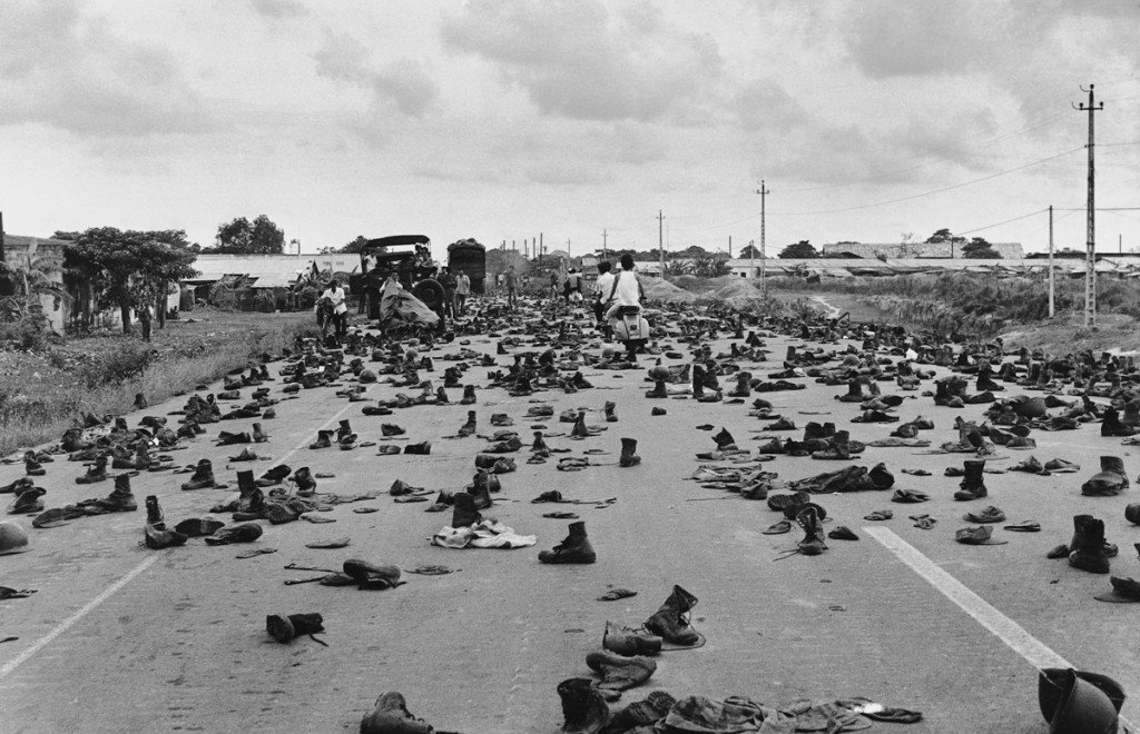 """April 30, 1975 Combat boots litter the road on the outskirts of Saigon, abandoned by ARVN soldiers who shed their uniforms to hide their status. """"I'll never forget the shoes and the loud 'thump, thump, thump' sound as we drove over them,"""" recalled the photographer. """"Decades of war were over and we finally had peace."""" IMAGE: DUONG THANH PHONG/ANOTHER VIETNAM/NATIONAL GEOGRAPHIC BOOKS"""